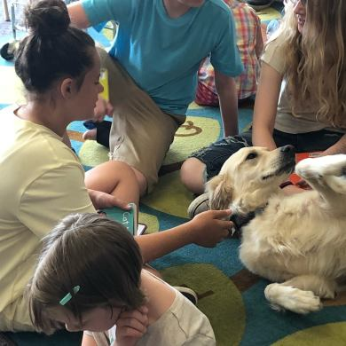 Image of children petting service dog from a previous Dog Tales event