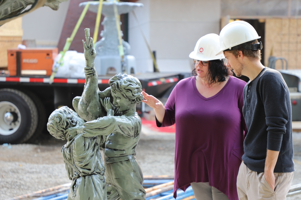Programming and Outreach Manager Jamie long shows Programming Specialist Zach Heimach the fountain's topper, which features two boys and a duck at the top.