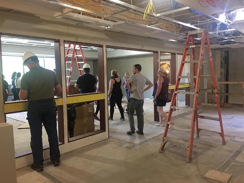 Numerous staff look into the Close Community Room, which will now be easier to access with one central, wide door.