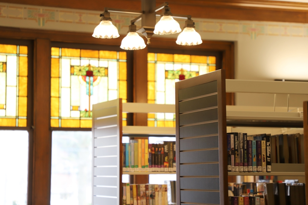 Photo of our new fiction shelves on the main floor, with the library's stained glass windows in the back.